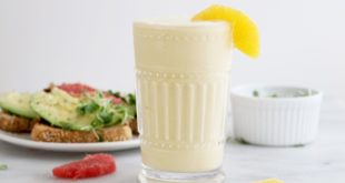 Citrus avocado toast and smoothie with citrus slices on the side.